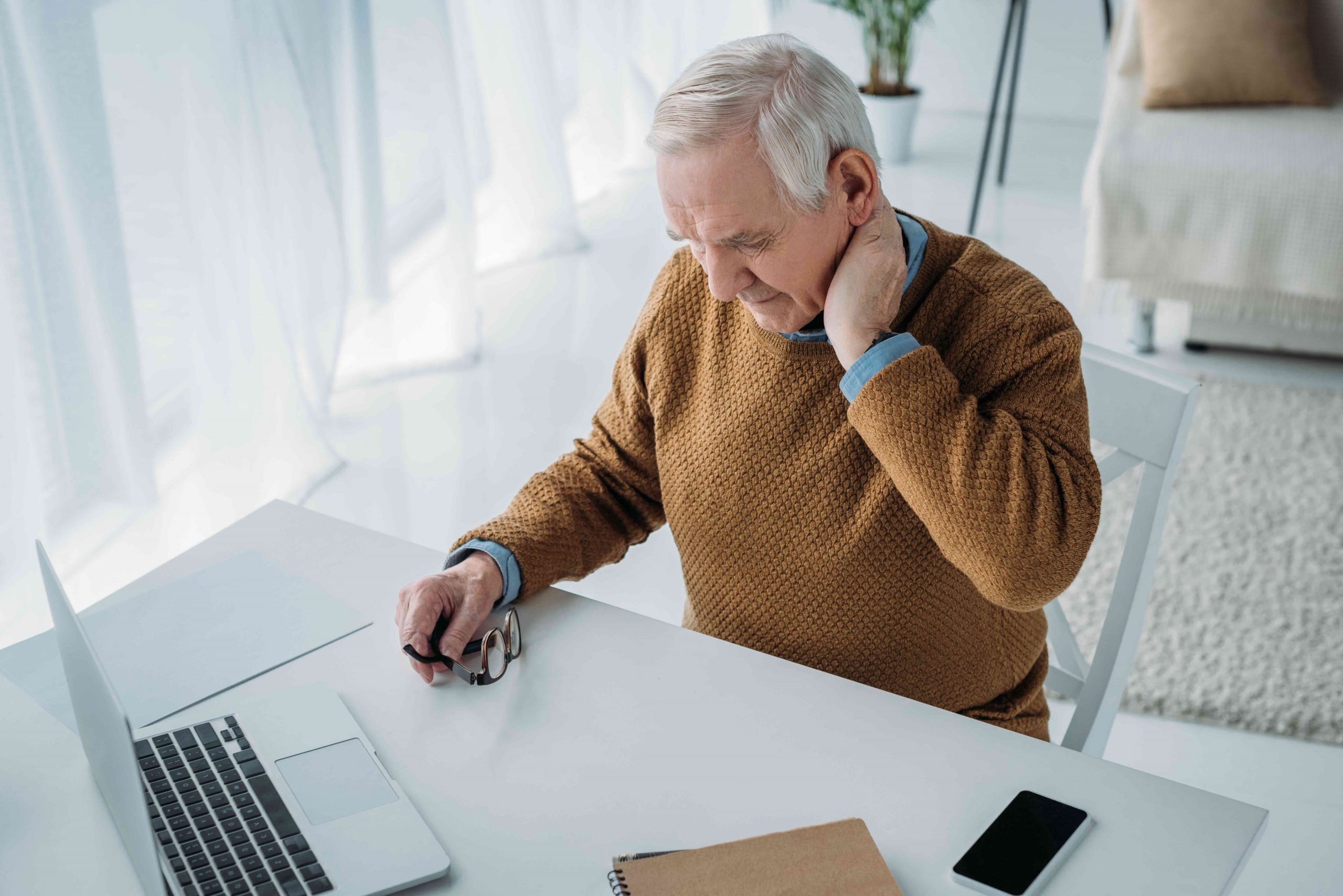 Senior man working in office and suffering from pain in neck